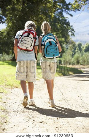 Teenage Couple Hiking Through Countryside Viewed From Back