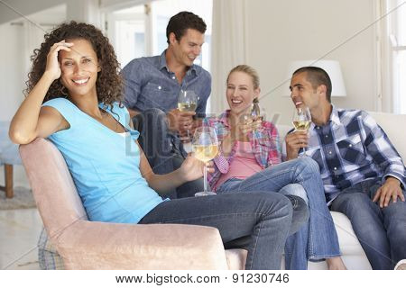 Group Of Friends Relaxing On Sofa Drinking Wine At Home Together