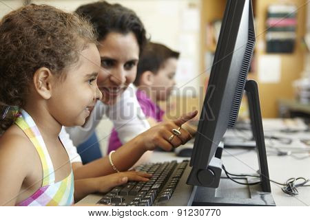 Elementary School Pupil With Teacher In Computer Class