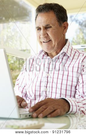 Senior Hispanic Man Using Laptop In Home Office