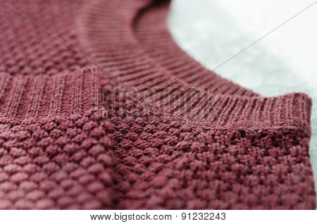 knitted burgundy sweater on white background