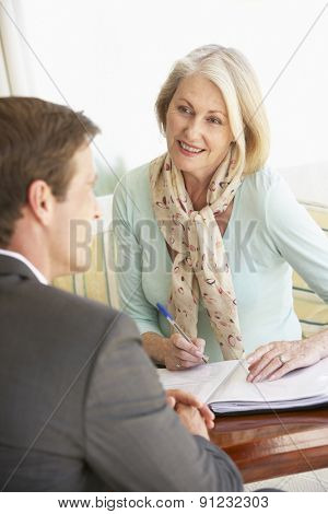 Senior Woman Meeting With Financial Advisor At Home
