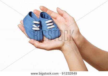 Children's Shoes In The Women's Hands