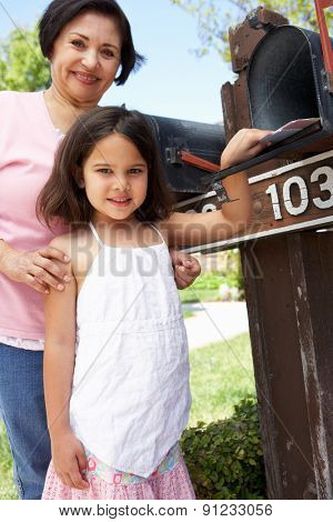 Hispanic Grandmother And Granddaughter Checking Mailbox