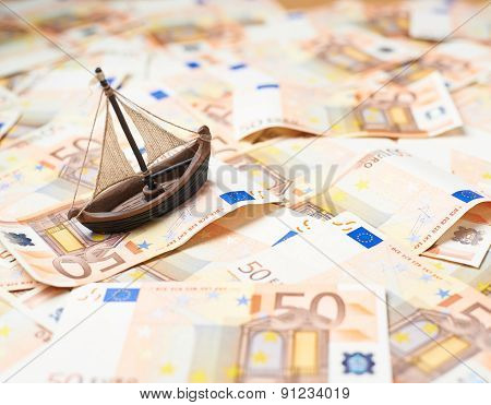Tiny ship over the bank note bills
