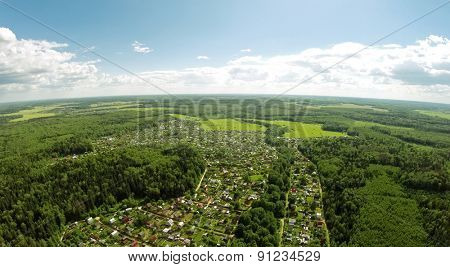 Cottage village among forest at summer sunny day. Aerial view
