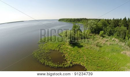 Shore of water reservoir with forest under blue sky at sunny summer day. Aerial view.
