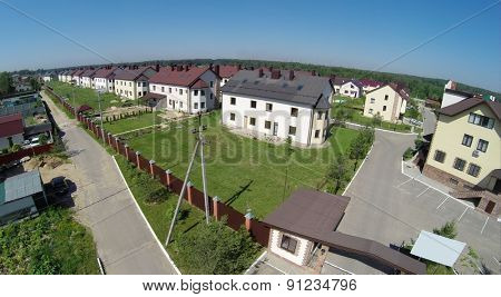 Cottage settlement near forest at sunny summer day. Aerial view