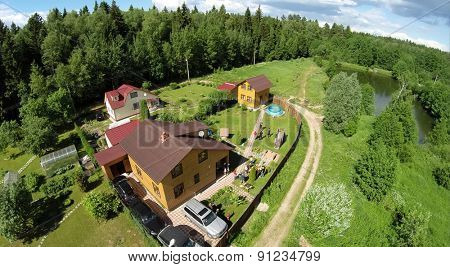 Cottage settlement with family get rest on yard at summer sunny day. Aerial view