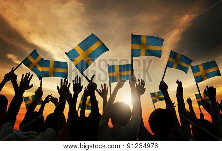 Group of People Waving Swedish Flags in Back Lit Concept
