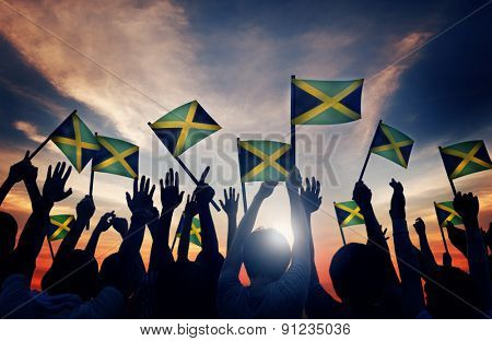 Group of People Waving Flag of Jamaica in Back Lit Concept