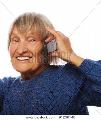 Smiling old lady communicating through mobile phone and thumb up