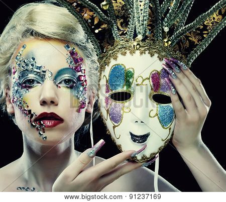 Portrait of woman with artistic make-up holding mask
