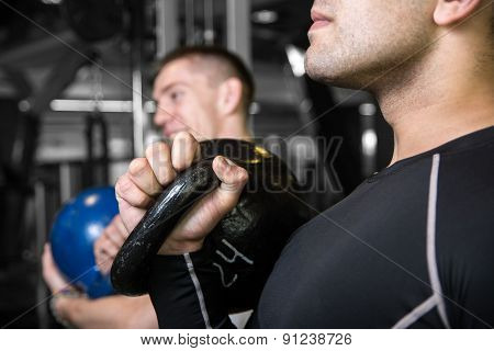 Close-up Kettlebell Swing Training Of Two Young Men In The Gym.