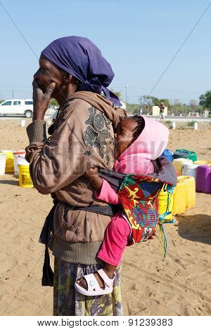 Small Namibian Child On The Back Of His Mother