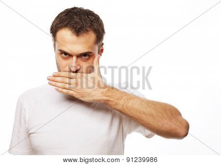 life style  and people concept: Shocked young man  covering mouth with hands and looking at camera while standing against white background