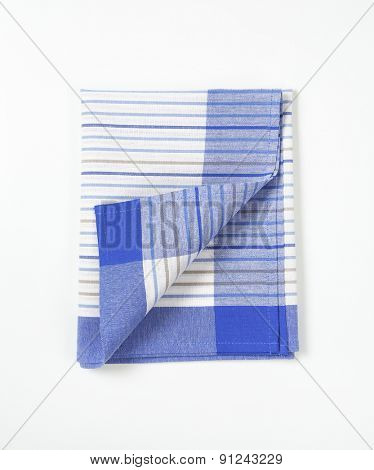 blue and white striped dishtowel on white background