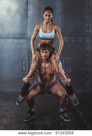 Athlete muscular sportsman doing exercising squats with woman sitting on his shoulders Crossfit fitn
