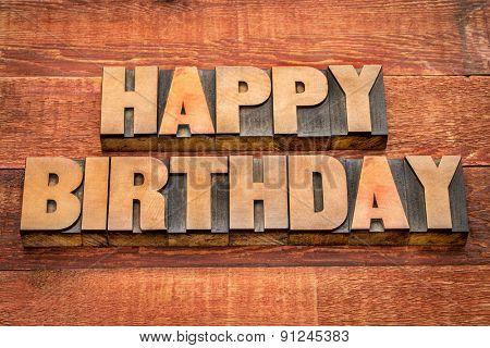 Happy Birthday greetings in letterpress wood type against rustic, red painted barn wood