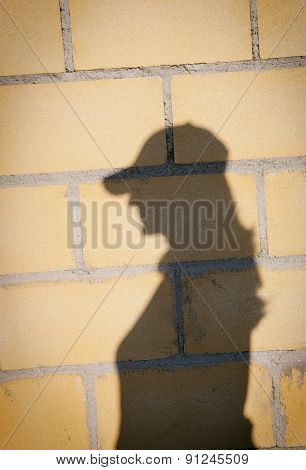 Shadow of a woman with hat on a yellow wall
