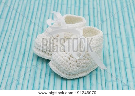 White Baby Booties On Grunge Background