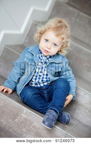 Little blond baby sitting on the stairs at home