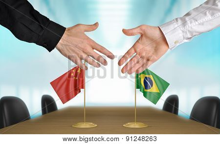 China and Brazil diplomats agreeing on a deal