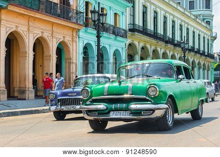 HAVANA,CUBA - MAY 20,2015 :  Vintage american cars next to colorful traditional buildings in Old Havana
