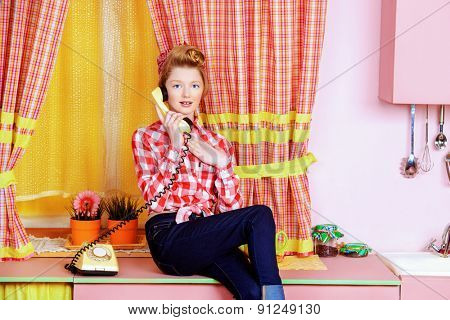Pretty teen girl talking on the phone on a pink kitchen. Beauty, youth fashion. Pin-up style.