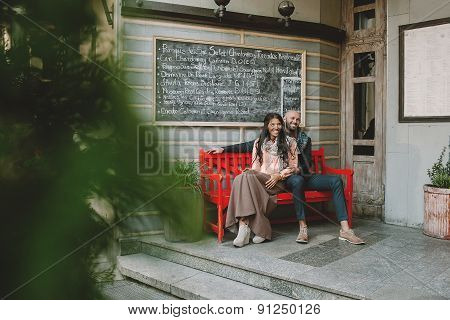Young Couple Sitting At Red Bench Near Cafe In The City