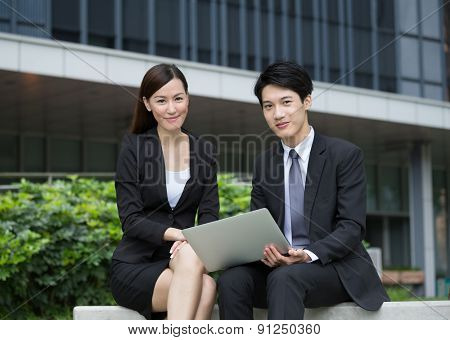 Businesswoman use laptop computer with businessman