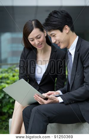 Businesswoman and man look at the laptop computer at outdoor