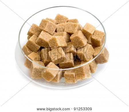 Brown sugar in a glass sugar bowl isolated on a white background