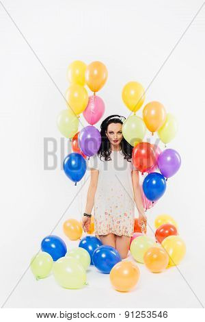 beautiful brunette girl with curly hair and balloons on white background