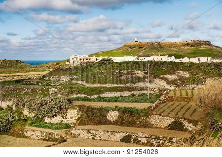 Panoram View On Fields And Lighthouse On The Top Of Mountain. Gozo Island, Malta.