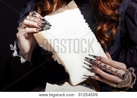 beautiful hands with long black nails holding the white sheet