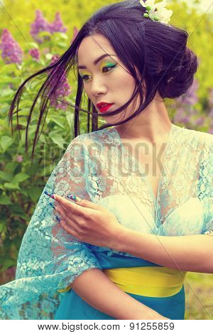 Chinese beautiful sexy girl in a kimono with a beautiful makeup with hair walking in a garden near