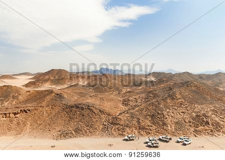Beautiful Desert Landscape Of Egypt. Safari Cars Go On The Road Between Mountains.