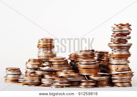 Big Heap Of Columns Of Different Coins On White Background.