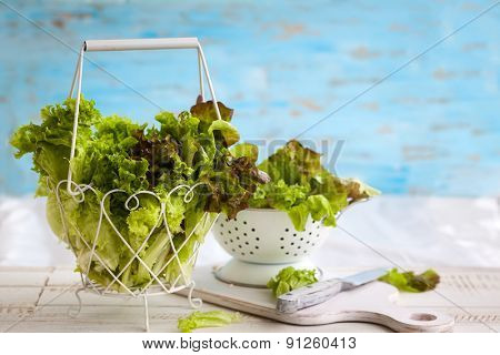 Various types of lettuce in a basket on the wooden table