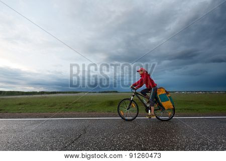 Young lady hiker with loaded bicycle riding on the wet asphalt road