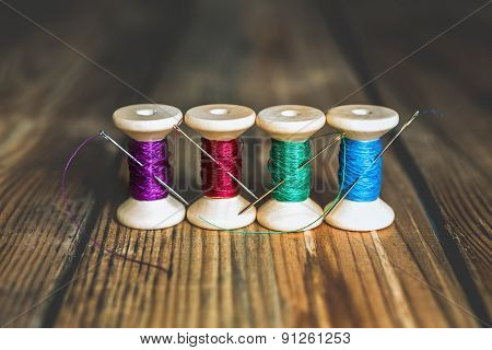 Spools Of Thread With Needles On Wooden Background. Old Sewing Accessories. Colored Threads