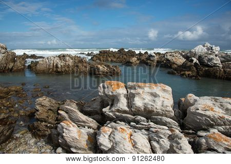 Rocks In The Sea At Cape Agulhas With Waves Breaking In The Background