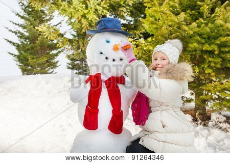 Girl making snowman putting carrot as his nose