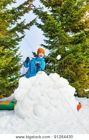 Laughing boy in blue winter jacket plays snowballs