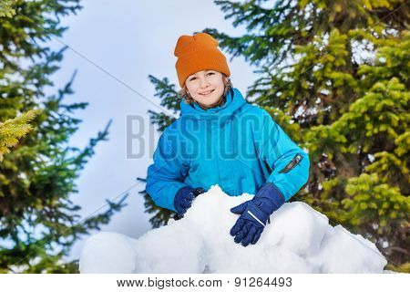 Cute child building snow fortress closeup