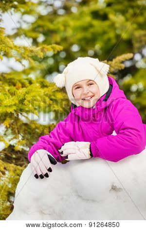 Close-up of happy girl stands behind the snow wall