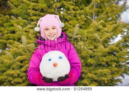 Portrait of girl holding snowman's head in forest