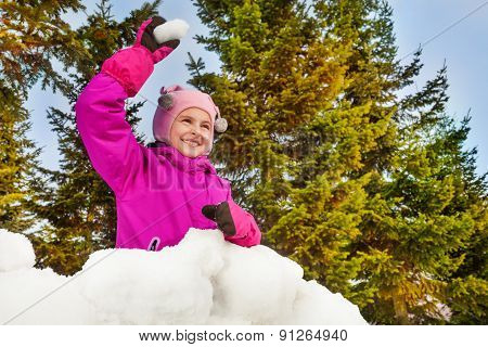 Girl ready to throw snowball in forest