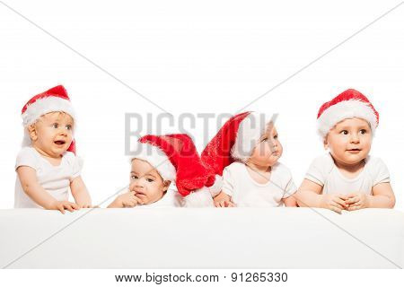 Four babies stand in a row wear red Christmas hats